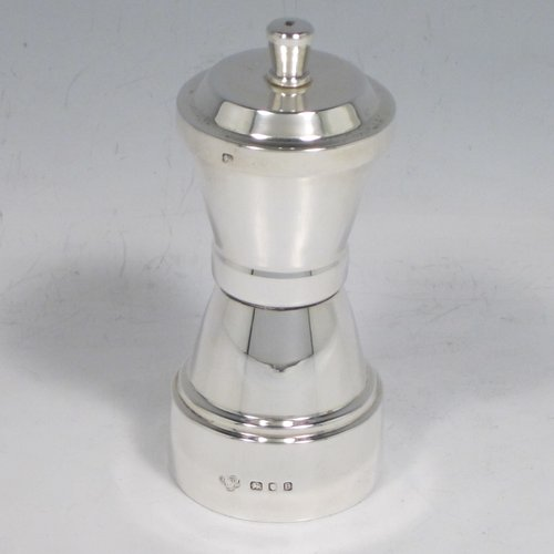 Sterling silver Art Deco pepper grinder, having a plain round body with sides tapering into a central band, a stepped cover with finial, and an original peugeot grinding mechanism. Made by Goldsmiths & Silversmiths of London in 1937. The dimensions of this fine hand-made silver pepper grinder are height 10 cms (4 inches), diameter at base 4.5 cms (1.75 inches), and it weighs approx. 100g (3 troy ounces).