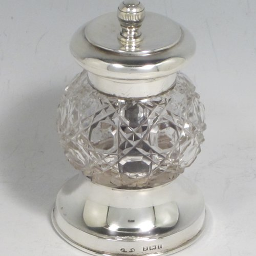 Antique Edwardian sterling silver and hand-cut crystal pepper grinder, having a round body with hobnail-cut pattern, plain round mounts top and bottom, and an original Peugeot grinding mechanism. Made John Grinsell of Birmingham in 1905. The dimensions of this fine hand-made silver and crystal pepper grinder are height 9 cms (3.5 inches), and diameter at base 6 cms (2.25 inches).