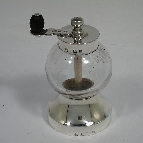 A handsome Antique Edwardian Sterling Silver and hand-blown crystal pepper grinder, having a plain round body with plain mounts top and bottom, a side-winding grinder arm with wooden finial, and an original Peugeot grinding mechanism. Made by Heath and Middleton of Birmingham in 1902. The dimensions of this fine hand-made antique silver and crystal pepper grinder are height 9.5 cms (3.75 inches), and diameter at base 5.5 cms (2.25 inches).