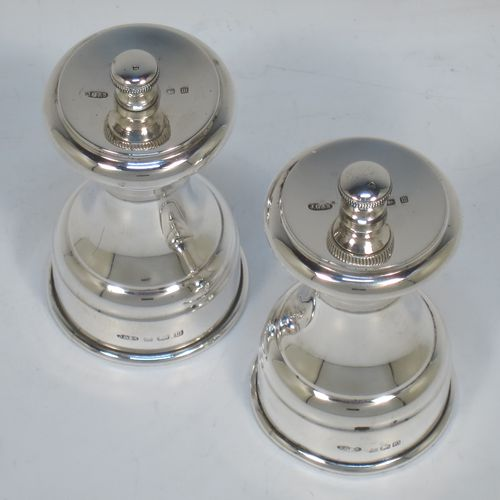 A very handsome pair of Antique Sterling Silver pepper grinders, having plain round baluster bodies, with original grinder mechanisms, and knurled finials. Made by John Grinsell and Sons of Birmingham in 1911. The dimensions of this fine pair of hand-made antique silver pepper grinders are height 8.5 cms (3.25 inches), diameter at bases 4.5 cms (1.75 inches), and they weigh approx. 186g (6 troy ounces).