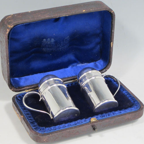 An Antique Victorian Sterling Silver pair of kitchen pepper pots, having plain round cylindrical bodies, with hand-pierced pull-off lids, scroll side-handles, sitting on flat bases, and all in their original blue satin and velvet-lined presentation box. Made in Birmingham in 1895. The dimensions of these fine hand-made antique silver pepper pots are height 6.5 cms (2.5 inches), length 5 cms (2 inches), and they weigh a total of 58g (1.9 troy ounces).