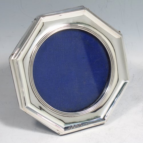 An Antique Sterling silver photograph frame, having a hand-made plain octagonal body and round aperture, with reeded borders, and pinned to a black leather-backed easel frame. Made by the Dixon Brothers of Birmingham in 1911. The diameter of this fine hand-made silver photo frame is 7.5 cms (3 inches).