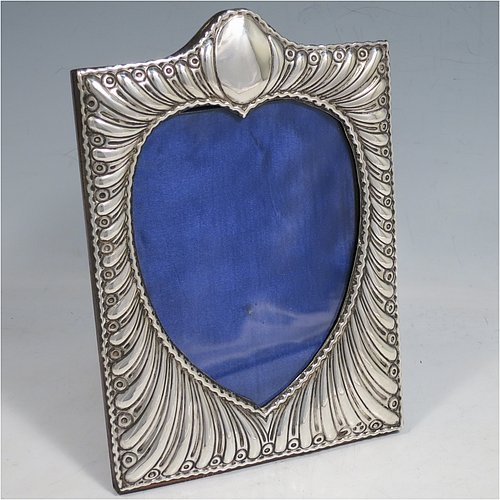 A very pretty Antique Victorian Sterling Silver photograph frame, having a heart-shaped aperture, surrounded by a hand-chased body with fluted decoration, and a wood-backed easel frame with brass fittings. Made by William Comyns of London in 1898. The internal dimensions of this fine hand-made antique silver photo frame are 12.5 cms (5 inches) high by 9.5 cms (3.75 inches) wide.