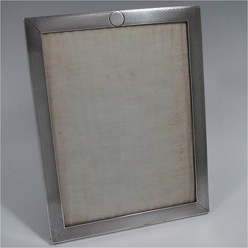 A Sterling Silver portrait photograph frame, having a hand-made rectangular body with machine-engraved and patterned border, a vacant round cartouche on the top border, and a brown wood-backed easel frame. Made by Percy James Finch of Birmingham in 1924. The dimensions of this fine hand-made silver photo frame are height 20 cms (8 inches), and width 15 cms (6 inches).