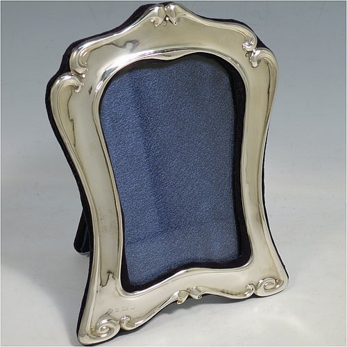 An Antique Victorian Sterling Silver Art Nouveau style portrait photograph frame, having a hand-chased body with scroll-work border, and a blue velvet-backed easel frame. Made by William Hutton of Birmingham in 1903. The internal dimensions of this fine hand-made antique silver photo frame are 12 cms (4.75 inches) high by 9 cms (3.5 inches) at the widest point.