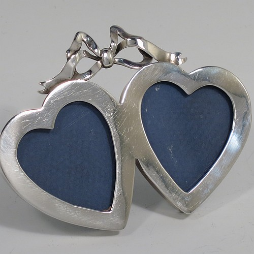 A rare Antique Victorian Sterling Silver double heart-shaped photograph frame, having two joined heart-shaped frames with plain borders, a top ribbon and bow finial, and an original green leather and easel backing. Made in London in 1898. The internal dimensions of each heart shape are 3.5 cms (1.3 inches) high, and 3cms (1.25 inches) wide.