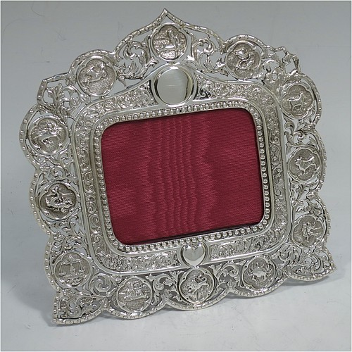 A very pretty and unusual Antique Victorian Sterling Silver photograph frame, having a rectangular aperture, surrounded by a bead and floral border with a lower heart-shaped cartouche and an upper round cartouche, all surrounded again by a hand-chased border with the twelve signs of the Zodiac, and a maroon velvet-backed easel frame. Made by Charles Boyton of London in 1888. The internal dimensions of this fine hand-made antique silver Zodiac sign photo frame are 9.5 cms (3.75 inches) wide by 7.5 cms (3 inches) high.