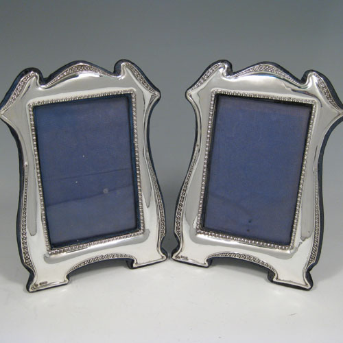 Sterling silver pair of photo frames with blue velvet backs, made in Birmingham in 1916. Dimensions 13 cms (5.15 inches) x 8.3 cms (3.5 inches).