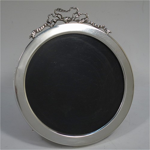 A very pretty Antique Edwardian Sterling Silver  photograph frame, having a plain round body with straight sides, an applied cast ribbon and bow top, and a brown wood-backed easel frame. Made by Stokes and Ireland Ltd., of Chester in 1905. The internal dimensions of this fine hand-made antique silver photo frame are diameter 11 cms (4.25 inches).