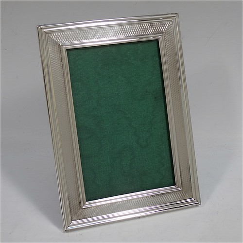 A handsome Antique Sterling Silver portrait photograph frame, having a hand-made rectangular body, a hand-chased border with engine-turned decoration and reeded edges, and an original dark brown leather-backed easel frame. Made by the Gorham Manufacturing Company of Birmingham in 1915. The internal dimensions of this fine hand-made antique silver photo frame are height 13 cms (5.25 inches), and width 8.5 cms (3.3 inches).