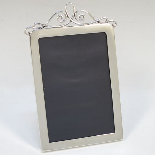 A handsome Antique Edwardian Sterling Silver portrait photograph frame, having a plain hand-made rectangular body with rounded top corners, a pretty applied wire-work top mount, and a maroon leather-backed easel frame. Made by J. Batson and Sons of London in 1902. The internal dimensions of this fine hand-made antique silver photo frame are height 13 cms (5.25 inches), and width 9 cms (3.5 inches).