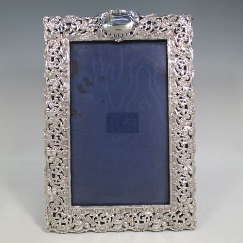 A large and very pretty Antique Edwardian Sterling Silver Art Nouveau style photograph frame, having a hand-chased body with flowers and scroll decoration, an inner bamboo style border, a top central vacant oval cartouche, and an original dark blue easel frame. Made by Simpson and Son of Birmingham in 1902. The internal dimensions of this fine hand-made antique silver photo frame are 27.5 cms (10.75 inches) high by 16.5 cms (6.5 inches) wide.