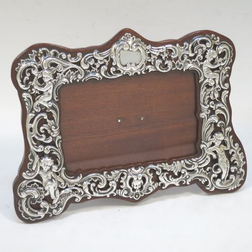 A very pretty Antique Edwardian Sterling Silver photograph frame, having a rectangular landscape aperture, surrounded by a hand-pierced border with cherubs, scroll-work, and floral decoration, and all pinned to a wood-backed easel frame. Made by William Comyns of London in 1902. The internal dimensions of this fine hand-made antique silver photo frame are 11 cms (4.5 inches) wide by 7 cms (2.75 inches) high.