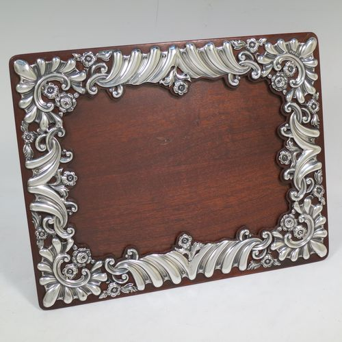 A very pretty Antique Victorian Sterling Silver photograph frame, having a rectangular landscape aperture, surrounded by a hand-pierced border with fluting, scroll-work, and floral decoration, and all pinned to a wood-backed easel frame. Made by William Comyns of London in 1895. The internal dimensions of this fine hand-made antique silver photo frame are 19 cms (7.5 inches) wide by 14 cms (5.5 inches) high.