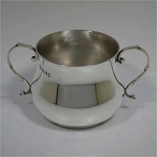 A very handsome Sterling Silver porringer, having a plain round bellied body, two scroll side handles, and sitting on a flat base. Made by Goldsmiths and Silversmiths of London in 1934. The dimensions of this fine hand-made silver porringer are height 7.5 cms (3 inches), spread across arms 13.5 cms (5.3 inches), and it weighs approx. 185g (6 troy ounces).