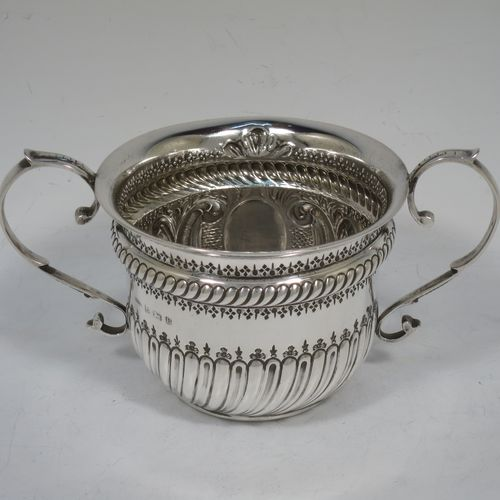 A very handsome Antique Sterling Silver porringer, having a round bellied body with hand-chased fluted and scroll decoration, with a vacant oval cartouche on one side, two scroll side-handles, and sitting on a flat base. Made by S. Blanckensee and Son Lt., of Birmingham in 1919. The dimensions of this fine hand-made antique silver porringer are height 8 cms (3.25 inches), spread across handles 16.5 cms (6.5 inches), and it weighs approx. 200g (6.5 troy ounces).