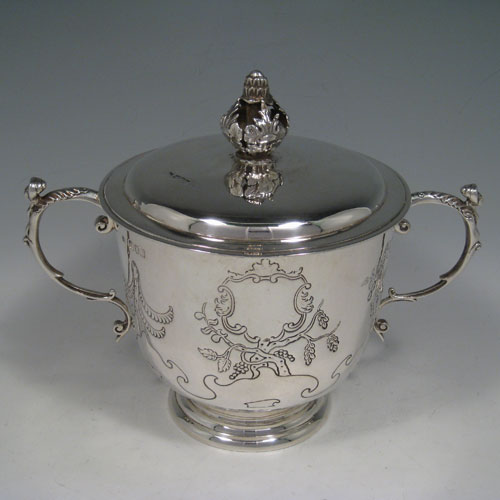 Antique Edwardian sterling silver hand-chased porringer with cast figural handles, cast floral finial, and floral hand-chasing. Made by Skinner and Co., of London in 1904. Height 19 cms (7.5 inches), spread across arms 24 cms (9.5 inches). Weight approx. 777g (25 troy ounces).