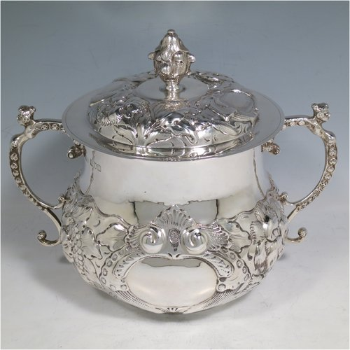 An Antique Victorian Sterling Silver porringer and cover, having a round baluster body, with hand-chased floral decoration, two cast figural scroll side handles, a pull-off cover with cast finial, and all sitting on a flat base. Made by Carringtons & Co., of London in 1906. The dimensions of this fine hand-made silver porringer are height 19 cms (7.5 inches), spread across arms 23.5 cms (9.25 inches), and it weighs approx. 885g (28.5 troy ounces).