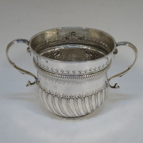 A very handsome Antique Queen Anne Britannia Standard Silver porringer, having a round bellied body with hand-chased fluted and scroll decoration, with a round cartouche on one side, two scroll side-handles, and sitting on a flat base. Made by Timothy Ley of London in 1714. The dimensions of this fine hand-made antique Britannia silver porringer are height 11 cms (4.25 inches), spread across handles 18 cms (7 inches), and it weighs approx. 284g (9 troy ounces). Please note that this item has an engraved contemporaneous set of initials in the cartouche.