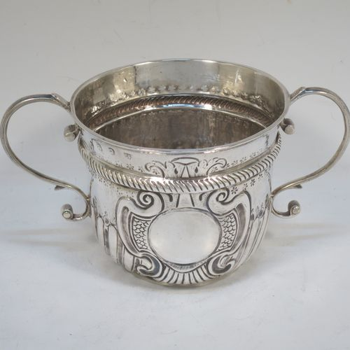 A very handsome Antique Queen Anne Britannia Standard Silver porringer, having a round bellied body with hand-chased fluted and scroll decoration, with a round cartouche on one side, two scroll side-handles, and sitting on a flat base. Made by Seth Lofthouse (Prob.) of London in 1709. The dimensions of this fine hand-made antique Britannia silver porringer are height 8 cms (3 inches), spread across handles 16 cms (6.25 inches), and it weighs approx. 156g (5 troy ounces).