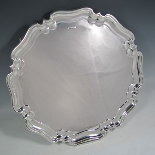 Sterling silver large serving salver, having a round body, with plain burnished ground, a pie-crust style border, and sitting on four scroll feet. Made by Henry Atkins of Sheffield in 1925. The dimensions of this fine hand-made silver salver are diameter 41 cms (16 inches), and it weighs approx. 1,837g (59 troy ounces).