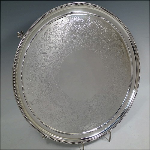A very pretty Antique Victorian Sterling Silver large salver, having an applied double bead-edged border, with a ground having hand-engraved ferns and song-bird decoration surrounding a central vacant round cartouche, and all sitting on four cast claw and ball feet. Made by Johnson, Walker, and Tolhurst of London in 1881. The dimensions of this fine hand-made antique silver salver are diameter 38 cms (15 inches), and it weighs approx. 1,615g (52 troy ounces).