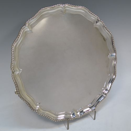 A very handsome Antique Edwardian Sterling Silver salver, having an applied shaped gadroon border, a plain ground, and sitting on three cast hoof feet. Made in London in 1904. The dimensions of this fine hand-made antique silver salver are diameter 33 cms (13 inches), and it weighs approx. 1,140g (37 troy ounces).