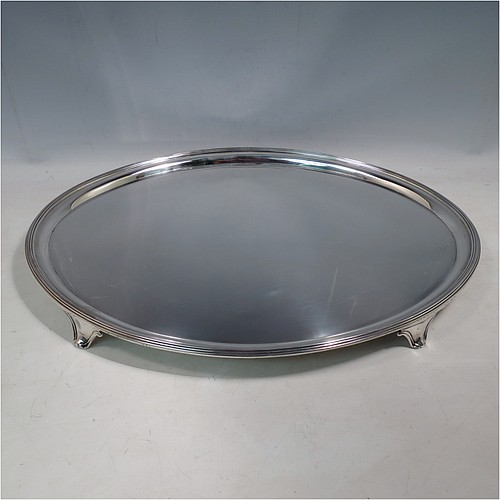 A large Antique Georgian Sterling Silver salver, having an oval body, with a plain burnished ground, an applied Reeded border, and sitting on four cast scroll feet. Made by William Bennett (Possibly) of London in 1801. The dimensions of this fine hand-made silver salver are length 46 cms (18 inches), width 35 cms (13.75 inches), and it weighs approx. 1,735g (56 troy ounces).