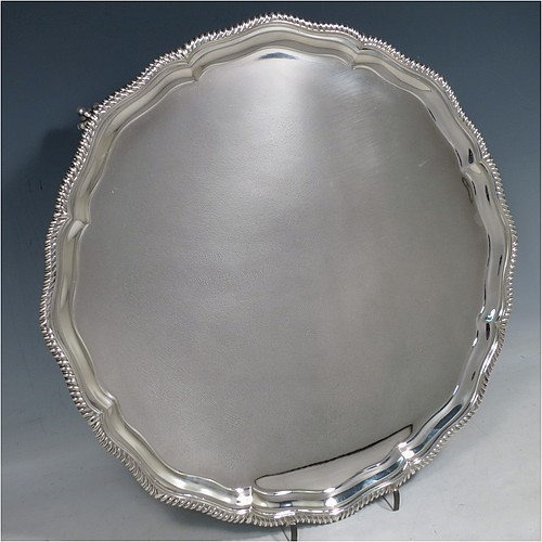 A large Sterling Silver salver, having a round body, with a plain burnished ground, an applied Shaped Gadroon border, and sitting on four cast claw and ball feet. Made by Thomas Bradbury & Sons of Sheffield in 1945. The dimensions of this fine hand-made silver salver are diameter 36 cms (14.25 inches), and it weighs approx. 1,333g (43 troy ounces).
