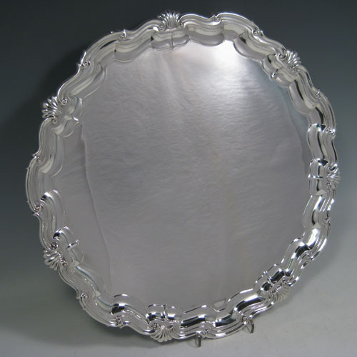 A very elegant Sterling Silver large salver, having an applied lobed and shell border, a plain ground, and sitting on four cast foliate feet. Made by James Dixon and Sons of Sheffield in 1924. The dimensions of this fine hand-made silver salver are diameter 36 cms (14 inches), and it weighs approx. 1,210g (39 troy ounces).