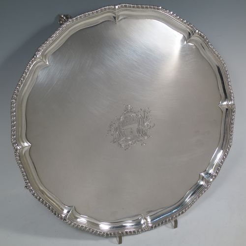 A very handsome Antique Georgian Sterling Silver salver, having an applied shaped gadroon border, a plain ground with a hand-engraved armorial central crest, and sitting on four cast claw and ball feet. Made by John Carter II of London in 1772. The dimensions of this fine hand-made antique silver salver are diameter 35 cms (13.75 inches), and it weighs approx. 1,270g (41 troy ounces).