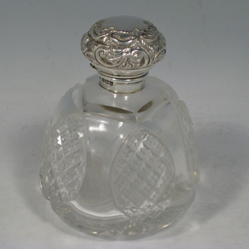 Antique Edwardian sterling silver and hand-cut crystal table scent bottle, having a hand-chased round mount with floral decoration, a hinged lid, an internal stopper, and hand-cut crystal main body. Made by A. W. Pennington of Birmingham in 1906. The dimensions of this fine hand-made silver and crystal scent bottle are height 10 cms (4 inches), and diameter 8 cms (3 inches).