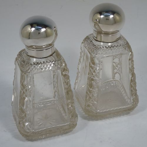 A very pretty and unusual pair of Antique Victorian Sterling Silver and hand-cut crystal table scent bottle, having plain round mounts  with hinged lids, gold-gilt interiors and internal stoppers. The crystal bodies with square cross-sections and tapering sides having clear side panels and hobnail cut edges, and all sitting on star-cut bases. Made by John Grinsell and Co., of London in 1898. The dimensions of these fine hand-made antique silver and crystal scent bottles are height 14.5 cms (5.75 inches), and 7cms (2.75 inches) square at base.