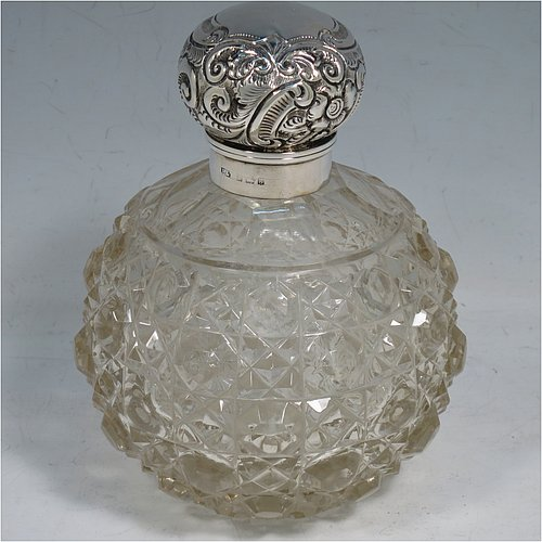 An Antique Edwardian Sterling Silver and hand-cut crystal table scent bottle, having a hand-chased round mount with floral decoration, a hinged lid, an internal stopper, and hand-cut crystal main body in the Hobnail pattern. Made by Hilliard & Thomason of Birmingham in 1906. The dimensions of this fine hand-made antique silver and crystal scent bottle are height 13 cms (5 inches), and diameter 9 cms (3.5 inches).