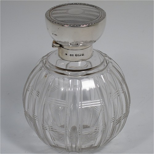 An Antique Sterling Silver and hand-cut crystal large table scent bottle, having a plain round mount, a hinged lid with an applied floral border and bands of engine-turned engraved decoration, an internal stopper, and a hand-cut crystal round main body with geometrical decoration. Made by Synyer and Beddoes of Birmingham in 1915. The dimensions of this fine hand-made antique silver and crystal scent bottle are height 11.5 cms (4.5 inches), and diameter 8 cms (3.25 inches).
