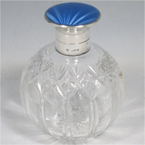 A Sterling Silver and hand-cut crystal table scent bottle, having a plain round mount, a hinged lid with a blue enamelled top, an internal stopper, and hand-cut main body with reeding and star-cut  decoration. Made by Albert Carter of Birmingham in 1926. The dimensions of this fine hand-made silver and enamelled scent bottle are height 11 cms (4.25 inches), and diameter 9 cms (3.5 inches).