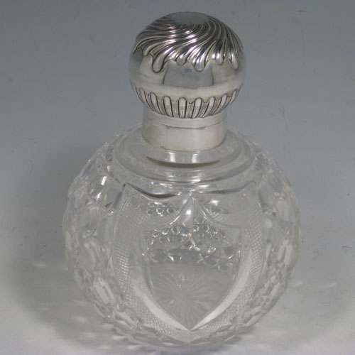 Antique Victorian sterling silver and hand-cut crystal large table scent bottle, having a hand-chased round mount with swirl-flute decoration, a hinged lid, an internal stopper, and hobnail cut main body with a shield-shaped cartouche. Made by James Dixon and Sons of Sheffield in 1901. The dimensions of this fine hand-made scent bottle are height 15 cms (6 inches), and diameter 11 cms (4.25 inches).