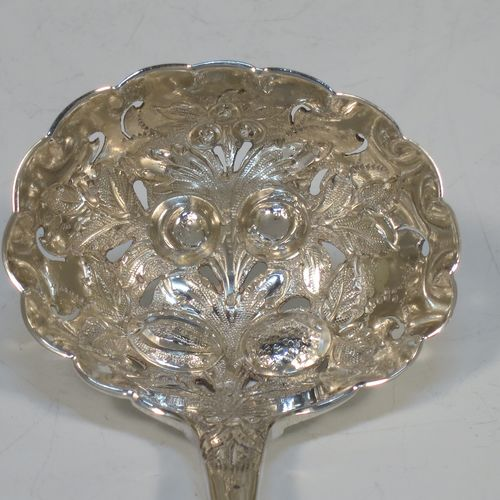 A very pretty Antique Victorian Sterling Silver sugar sifting ladle, having a hand-chased handle with floral decoration, and a hand-chased fluted bowl with fruit and floral decoration, all in its original maroon satin and velvet-lined presentation box. Made by Henry Holland of London in 1865. The dimensions of this fine hand-made antique silver sugar sifting ladle are length 16.5 cms (6.5 inches), and it weighs approx. 56g (1.8 troy ounces).
