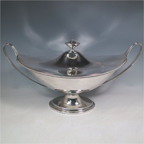 An Antique Georgian Sterling Silver large soup tureen in a boat-shape neoclassical style, having a very plain oval body with a pull-off lid and an urn-shaped finial, with applied gadroon borders, two reeded scroll side-handles, and all sitting on a pedestal foot. Made by Cornelius Bland of London in 1789. The dimensions of this fine hand-made antique silver soup tureen and cover are height 28 cms (11 inches), length including handles 52 cms (20.5 inches), width 25.5 cms (10 inches), and it weighs approx. 2,850g (92 troy ounces).
