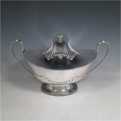 An Antique Edwardian Sterling silver soup tureen, having a pull-off lid with an urn-shaped finial and cut-out slot for a ladle, with hand-chased half-fluted decoration, applied gadroon borders, two reeded scroll side-handles, and all sitting on a pedestal foot. Made by Mappin & Webb of Sheffield in  1905. The dimensions of this fine hand-made antique silver soup tureen and cover are height 25 cms (9.75 inches), length including handles 39.5 cms (15.5 inches), width 21.5 cms (8.5 inches), and it weighs approx. 1,779 (57 troy ounces).