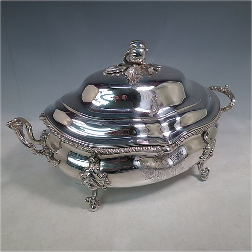 An Antique Early Victorian Sterling Silver soup tureen in a Regency style, having an oval bellied body with an applied wavy gadroon border, a domed pull-off cover with a cast pumpkin and leaf handle, with two cast scroll and shell side handles, and sitting on four cast scroll feet with floral shoulders. Made by William Moulson of London in 1840. The dimensions of this fine hand-made antique silver soup tureen and cover are length 43 cms (17 inches), height 25.5 cms (10 inches), width 24 cms (9.5 inches), and it weighs approx. 3,195g (103 troy ounces). Please note that this antique Victorian silver soup tureen is crested on the main body and cover.