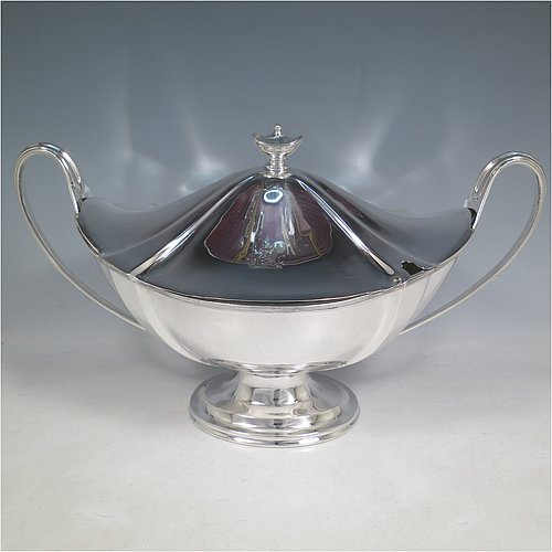 An Antique Edwardian Sterling silver Neoclassical style soup tureen, having a pull-off lid with an urn-shaped finial and cut-out slot for a ladle, with hand-chased shoulders, applied reeded borders, two reeded scroll side-handles, and all sitting on a pedestal foot. Made by Goldsmiths & Silversmiths  of London in 1902. The dimensions of this fine hand-made antique silver soup tureen and cover are height 23 cms (9 inches), length including handles 38 cms (15 inches), width 20 cms (8 inches), and it weighs approx. 1,615 (52 troy ounces). Please note that this item is crested on lid and body.