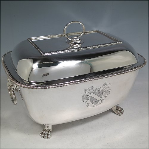 An Antique Georgian Sterling Silver soup tureen, having a plain rectangular body with rounded corners, a pull-off lid cover with an asparagus loop handle, with applied gadroon borders, two cast lion-mask loop side handles, and all sitting on four cast lions-paw feet. Made by William Bennett of London in 1805. The dimensions of this fine hand-made antique silver soup tureen and cover are height 21 cms (8.25 inches), length 28 cms (11 inches), width 20 cms (8 inches), and it weighs approx. 1,860 (60 troy ounces). Please note that this antique soup tureen is crested on one side.