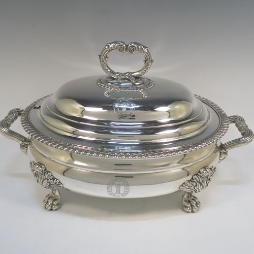 An Antique Georgian Sterling Silver Scottish soup tureen in a Regency style, having an oval plain baluster body with applied gadroon border, a domed pull-off cover with a cast anthemion leaf handle, with two cast scroll side handles, and sitting on four cast lions-paw feet with floral shoulders. Made in Edinburgh in 1815. The dimensions are height 24 cms (9.5 inches), and width (across handles) 42 cms (16.5 inches). Please note that this antique Regency silver soup tureen is crested on the main body and cover.