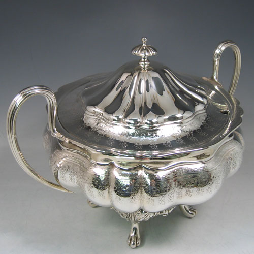 An Antique Victorian Silver Plated soup tureen, having a hand-chased and engraved body with melon-style lobes and floral decoration, a pull-off cover with cast finial, with two reeded loop side-handles, and all sitting on four cast foliate feet. Made by the Mappin Brothers in ca. 1870. The dimensions of this fine hand-made antique silver-plated soup tureen are height 26 cms (10.25 inches), and width (across handles) 37 cms (14.5 inches).
