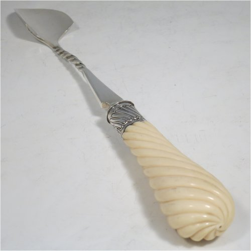 An Antique Victorian Sterling Silver and Ivory handled stilton cheese scoop, having a hand-cut spirally fluted handle, a hand-chased swirl-fluted ferrule, and a twisted stem with plain scoop. Made by William Hutton of London in 1899. The dimensions of this fine hand-made antique silver stilton cheese scoop are length 24 cms (9.5 inches).