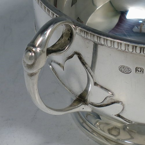 An Antique Sterling Silver sugar bowl, in a Georgian style, having a round bellied body, with unusual applied cut-card work and a gadroon border, two scroll side-handles, and all sitting on a pedestal foot. Made by Alexander Clarke & Co., of Birmingham 1913. The dimensions of this fine hand-made silver sugar bowl are height 7 cms (2.75 inches), spread across handles 15 cms (6 inches), and it weighs approx. 233g (7.5 troy ounces).