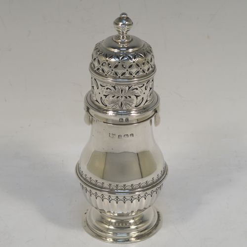 A heavy and very handsome Sterling Silver sugar caster, having a round bellied body with an applied reeded central girdle with hand-chased fluted decoration below, a hand-pierced lid with bayonet fit and cast urn-shaped finial, and sitting on a pedestal foot. Made by S. Blankensee and Sons Ltd. of Birmingham in 1929. The dimensions of this fine hand-made silver sugar caster are height 16 cms (6.3 inches), diameter of belly 6.5 cms (2.5 inches), and it weighs approx. 216g (7 troy ounces).