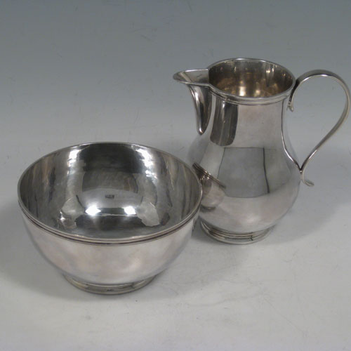 Sterling silver sugar and creamer set, having plain round baluster bodies, applied reeded borders, a sparrow-beak spout, and sitting on collet feet. Made by Padgett and Braham of London in 1962. The dimensions of this fine hand-made silver sugar and creamer set are height 10 cms (4 inches), diameter 10 cms (4 inches), and they weigh a total of approx. 290g (9.4 troy ounces).