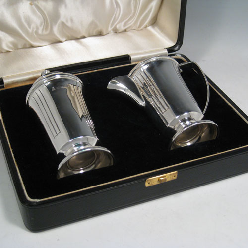 Sterling silver pair of Art Deco sugar caster and creamer set, having plain round bodies with tapering sides and reeded hand-chased decoration, a pull-off hand-pierced lid on the caster and a loop handle on the creamer, all sitting on round pedestal feet, and in their original satin and velvet-lined presentation box. Made in Birmingham in 1938. The dimensions of this fine hand-made silver sugar caster and cream jug set are height of caster 14 cms (5.5 inches), length of cream jug (11 cms (4.3 inches), and the total weight is approx. 217g (7 troy ounces).